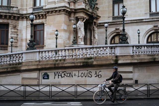 Người biểu tình viết dòng chữ ám chỉ Tổng thống Macron tương tự vị vua trị vì thời cách mạng Pháp lên bức tường tại nhà hát Palais Garnier ở Paris. (Ảnh: AP)