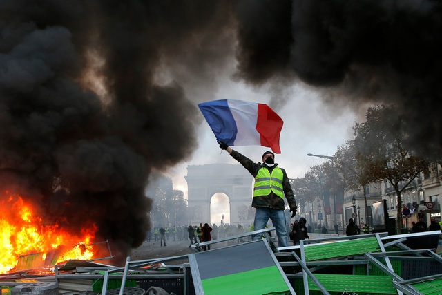 Người biểu tình cầm cờ đứng trên đống đổ nát tại Paris. (Ảnh: Reuters)