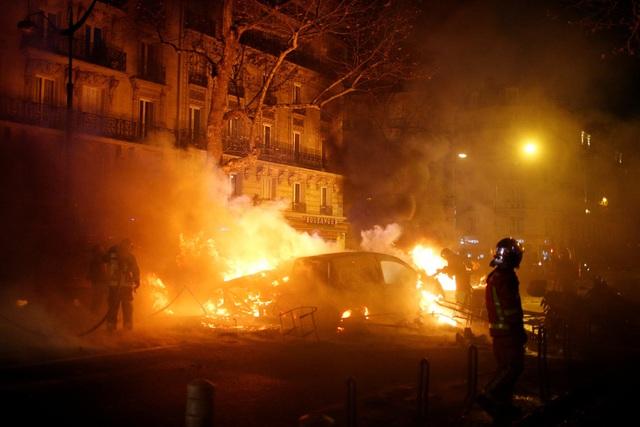 Lính cứu hỏa dập đám cháy do xe ô tô bị đốt ở Paris trong các cuộc biểu tình của phong trào Áo vàng. (Ảnh: Reuters)