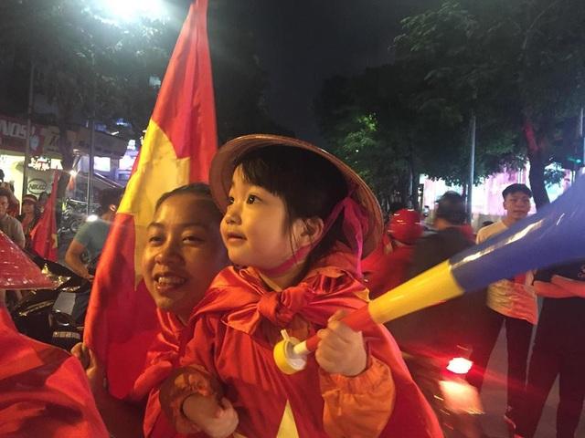 Trẻ nhỏ theo người lớn đi ăn mừng chiến thắng cho đội tuyển Việt Nam.