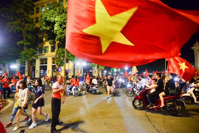 Một cổ động viên phất lá cờ đỏ sao vàng tự hào dân tộc.