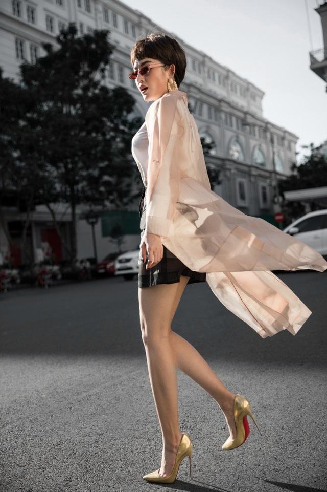 Phong cách áo choàng trong suốt gợi cảm đến chóng mặt cũng được Huyền My lăng-xê trong bộ ảnh lần này khi kết hợp cùng set đồ cơ bản là chân váy xuyên thấu màu đen và áo sơ-mi trắng.