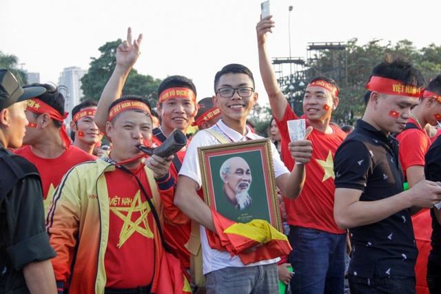 Một cổ động viên cầm ảnh Bác Hồ và cờ Tổ quốc xếp hàng vào sân cổ vũ cho đội tuyển Việt Nam.