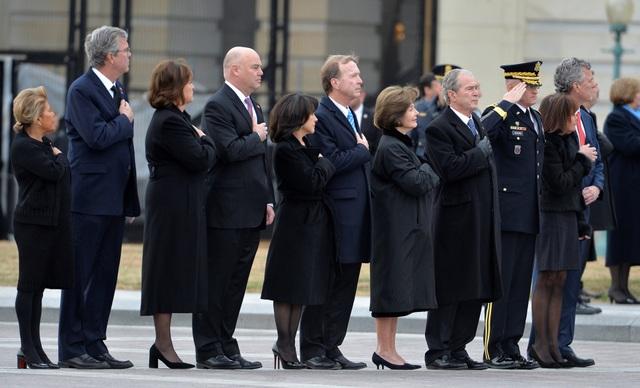 """Cựu Tổng thống George W. Bush cùng phu nhân và các thành viên trong gia đình cố Tổng thống Bush """"cha"""" đã đặt tay lên ngực khi đội danh dự chuyển linh cữu lên xe để tới Nhà thờ Quốc gia."""