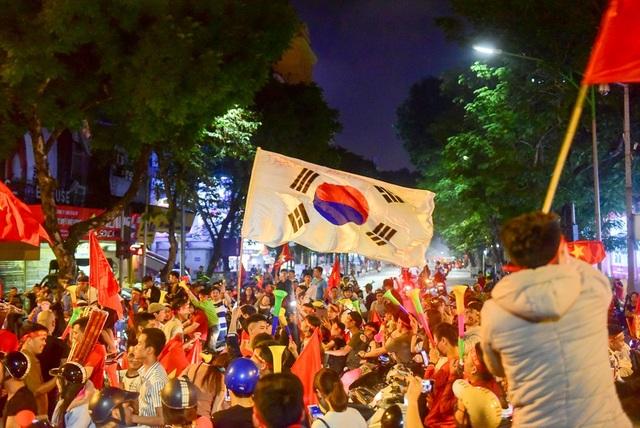 Không chỉ có lá cờ đỏ sao vàng, nhiều người còn cầm theo lá cờ nước Hàn Quốc quê hương cửa HLV Park Hang-seo.