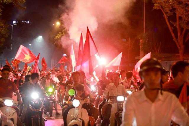 Người hâm mộ đốt pháo sáng ăn mừng trong tiếng reo hò.