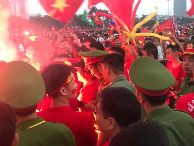 Đám đông hò hét và đốt pháo sáng ngay trước mặt lực lượng chức năng, nhưng rất khó phát hiện là ai vì số lượng CĐV quá đông.