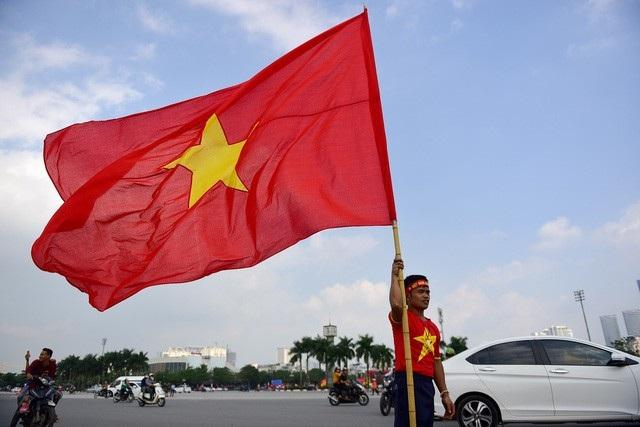 Một cổ động viên chuẩn bị lá cờ Tổ quốc lớn để tham gia diễu hành cùng đoàn. ảnh: Toàn Vũ