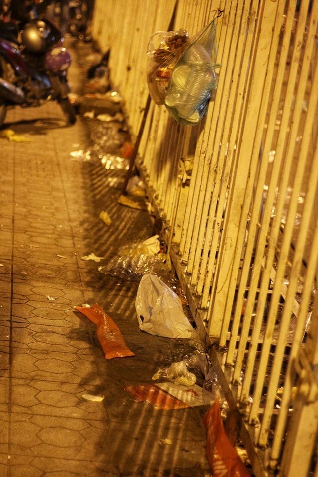 Rác mắc đầy trong khe dãy hàng rào chắn trước cổng sân vận động