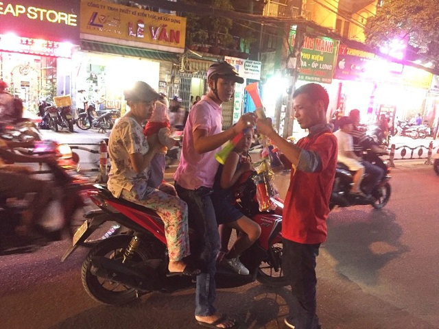 Một gia đình đổ ra đường ăn mừng chiến thắng của đội tuyển Việt Nam và dừng lại mua kèn.