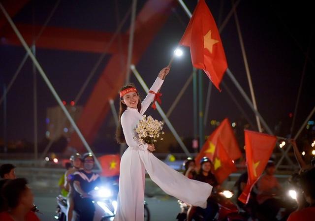 Thiếu nữ mặc áo dài vẫy cờ cổ vũ tuyển Việt Nam trên cầu Bình Lợi