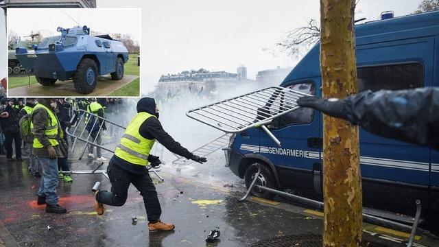 Một người biểu tình Áo vàng ném thanh chắn hàng rào trong cuộc biểu tình tại Paris. (Ảnh: Reuters)