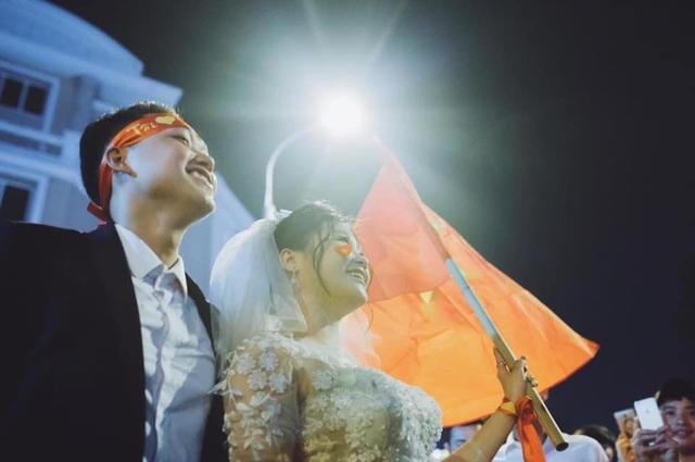 Dù vô tình nhưng cô dâu, chú rể cho biết may mắn lại được hòa vào biển người ăn mừng chiến thắng. Ảnh: Hoàng Ken