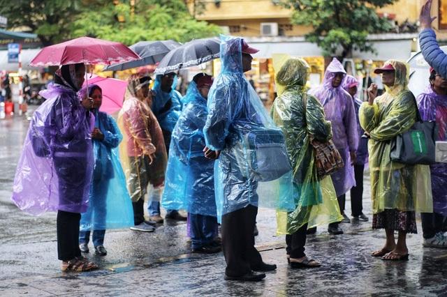 Đoàn khách du lịch tham quan trên phố đi bộ trong thời tiết mưa rét, không được ngắm nhìn trọn vẹn vẻ đẹp của Hồ Gươm vì trời tối và mưa kéo dài nhiều giờ.