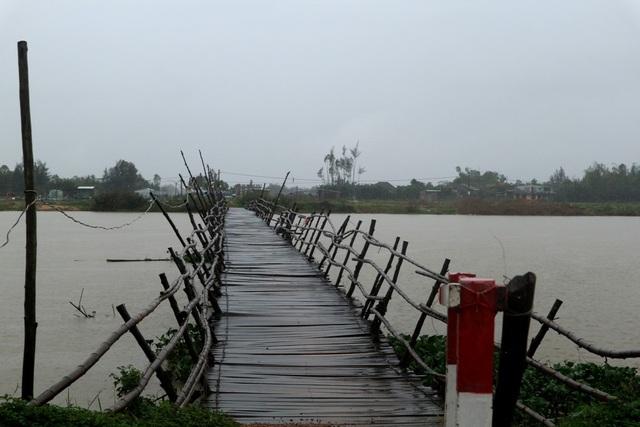 Nước sông dâng cao, cầu gỗ ọp ẹp khiến người dân không dám qua cầu.