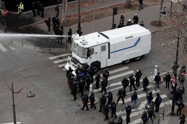 """Nước Pháp lại có thêm một cuối tuần không """"yên ả"""" khi khí hơi cay, khói lửa, hàng rào tràn ngập trên các tuyến đường chính. Cảnh tượng đập phá hỗn loạn tiếp tục được tái diễn. Trong ảnh: Vòi phun hướng về những người biểu tình quá khích."""
