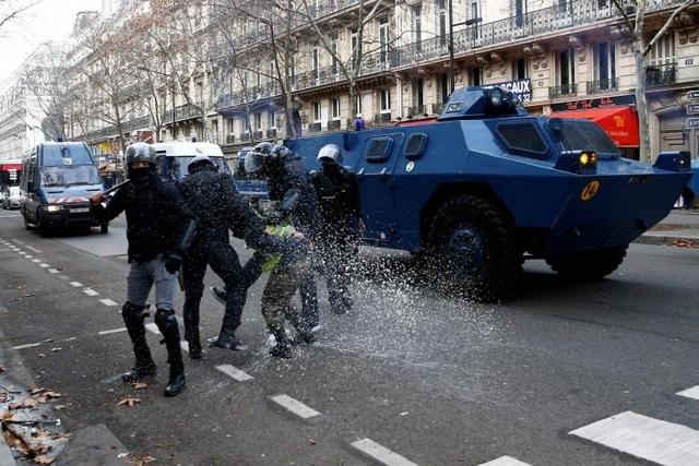 Theo RT, có 125.000 người đã xuống đường trên khắp nước Pháp, trong đó có 10.000 người ở thủ đô Paris. Chính quyền Pháp xác nhận họ đã bắt khoảng 1.300 người trên khắp cả nước. Hàng chục tới hàng trăm người bị thương. Trong ảnh: Xe bọc thép trên đường phố Paris.