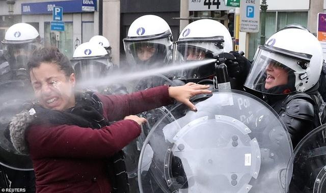 Một phụ nữ bị cảnh sát Bỉ xịt hơi cay khi cố xâm nhập vào khu vực không được phép vào (Ảnh: Reuters)