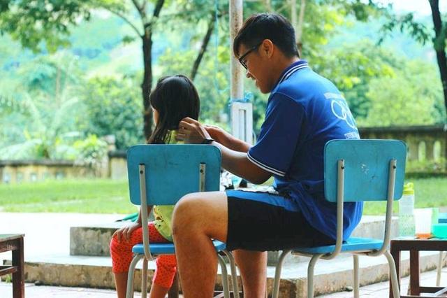 Nguyễn Hữu Lập cắt tóc cho các em học sinh trong một chương trình tình nguyện.