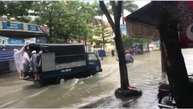 Xe tải giúp chở người và xe qua đoạn đường ngập nước.