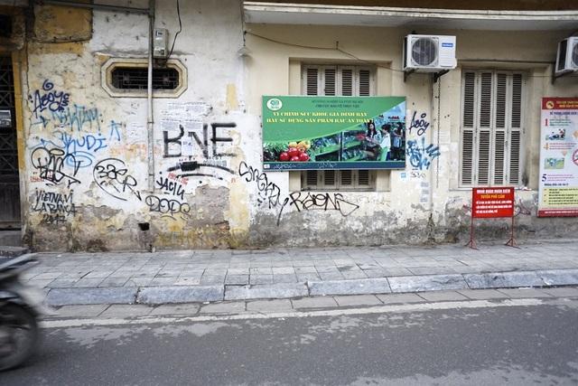 Một mảng tường phố Đinh Liệt bị vẽ đủ loại chữ nghĩa, nét vẽ sau chồng lên nét trước.