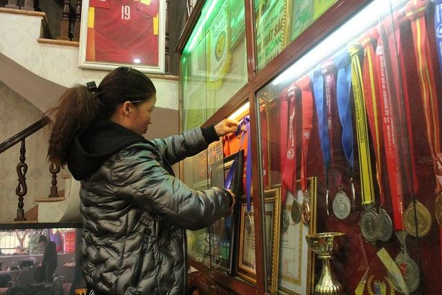 Mẹ Quang Hải cẩn thận xếp lại các huy chương, giải thưởng của con vừa được trao tặng