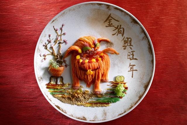 """Món gỏi cá thịnh vượng """"yusheng"""" thường được người Singapore ăn trong những ngày đầu năm mới. Món ăn trong hình được lấy cảm hứng từ hình tượng con nghê - một biến thể mang tính tâm linh từ chú chó vốn rất thân thuộc trong đời sống thường nhật của con người. Món """"yusheng"""" này được một khách sạn ở Singapore phục vụ với giá 999 đô la Singapore (SGD), tương đương 17 triệu đồng."""