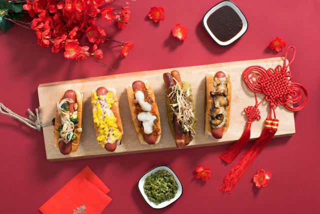 """Bánh mì kẹp xúc xích (""""hot dog"""" của người dân phương Tây) bỗng trở thành món ăn đường phố được nhiều người Singapore lựa chọn những ngày này. Đơn giản bởi trong tên tiếng Anh của món ăn này có từ… """"dog"""" (chú chó), vì vậy, nhiều người Singapore """"duy tâm"""" tin rằng đây là món ăn """"dân dã"""" thường ngày rất… may mắn trước thềm năm Tuất."""