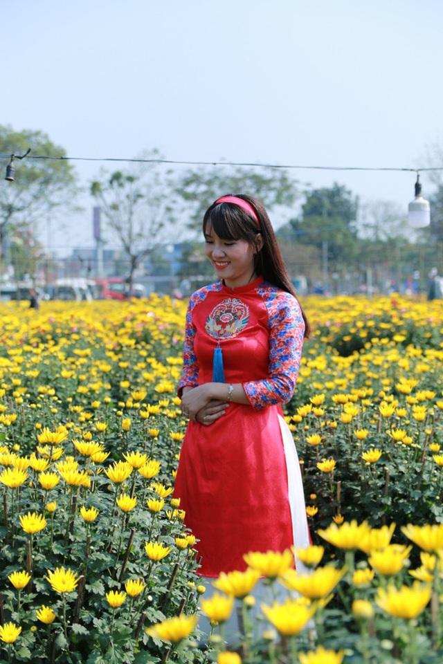 Thiếu nữ duyên dáng với tà áo dài truyền thống bên hoa cúc vàng