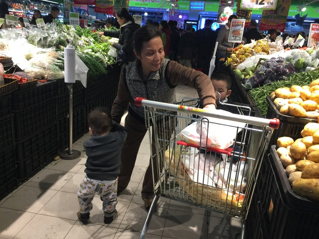 Chợ đông đúc nhưng không thể thiếu các em nhỏ theo mẹ, bà đi sắm tết