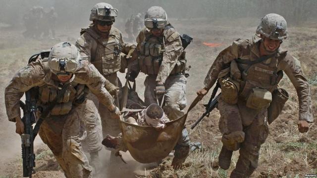 Lính thủy đánh bộ Mỹ khiêng đồng đội bị thương trong cuộc xung đột ở Afghanistan (Ảnh: Reuters)