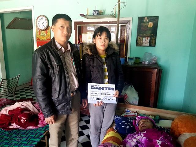 Đại diện lãnh đạo thị trấn Hà Lam, huyện Thăng Bình trao quà của bạn đọc đến em Linh
