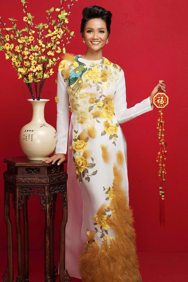 Hoa hậu H'hen Niê chọn chiếc áo màu trắng thêu họa tiết hoa vàng với biểu tượng con công được đính lông đặc biệt sang trọng.