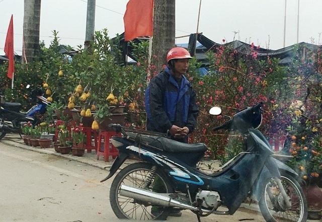 Những người làm dịch vụ vận chuyển thuê hoa, cây cảnh co ro trong giá rét chờ đợi kiếm mối.