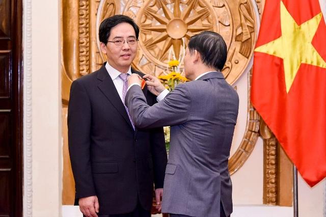 Thứ trưởng Bộ Ngoại giao Lê Hoài Trung gắn Huân chương Hữu nghị cho Đại sứ Hồng Tiểu Dũng