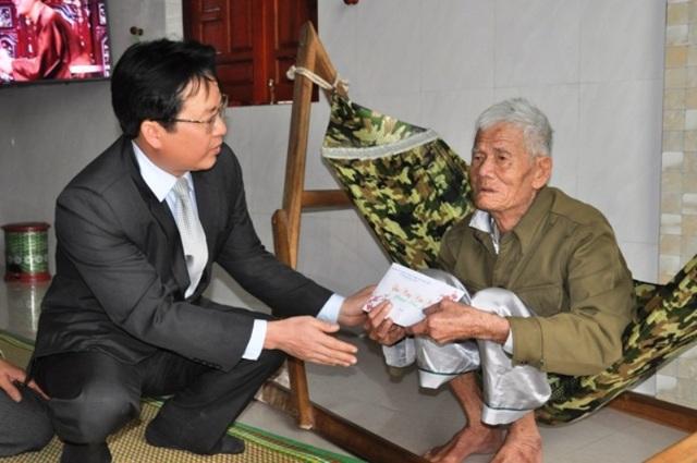 Ông Phạm Trung Đông, Chủ tịch UBND huyện Quảng Ninh tặng quà cho gia đình liệt sỹ Hoàng Văn Tuý, quê ở thôn Tân Định, xã Hải Ninh