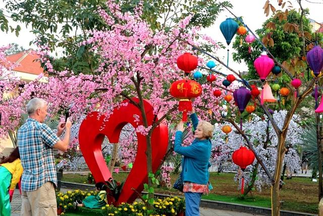 Du khách nước ngoài háo hức chụp ảnh kỷ niệm tại công viên Hội An với các mô hình Valentine và ngày Tết cổ truyền Việt Nam