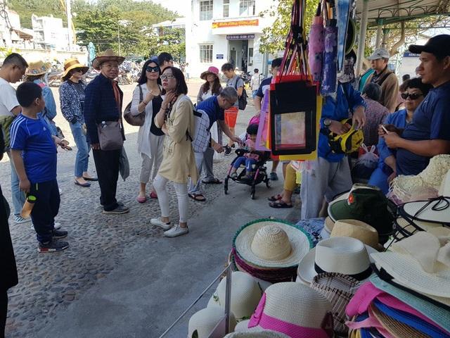 Du khách Trung Quốc bên một gian hàng bán mũ tại bến tàu Cầu Đá