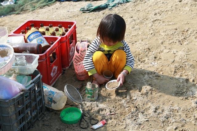 Một em bé hồn nhiên ngồi trên bờ chơi đùa để bố mẹ dọn dẹp. Không khí Tết đã cận kề nhưng tại đây dường như những gì liên quan tới sắm sửa, đồ mới, thức ăn, kẹo mứt vẫn thiếu thốn