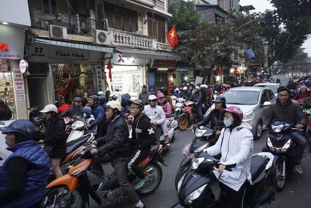 Từ chiều 29 Tết, phố xá Hà Nội đã vắng hơn song trục phố Hàng Ngang, Hàng Đào, Hàng Đường, Đồng Xuân vẫn đông đúc bởi lượng người đổ về mua sắm cả ngày.