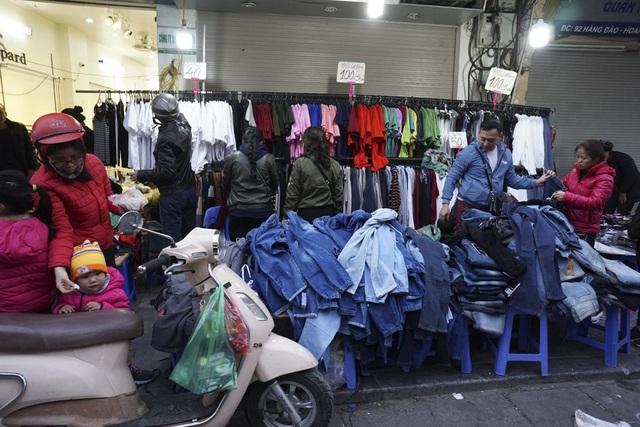 Ngồn ngộn áo quần được gắn mác giảm giá, xả hàng... gây sự chú ý cho người đi đường.