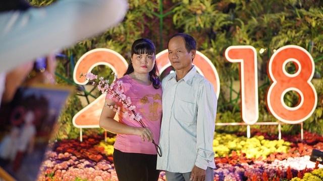 Một cặp vợ chồng đang nhờ thợ chụp ảnh dịch vụ lưu lại kỉ niệm với đường hoa Mậu Tuất