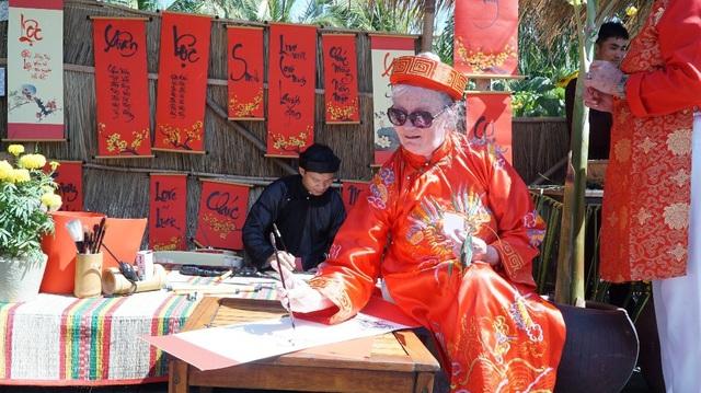Sau khi gói bánh chưng, vị khách này tự tay viết thư pháp ở phố ông Đồ