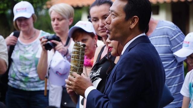 Ông Lê Phong Trần đang giới thiệu bánh tét truyền thống của người Việt cho du khách