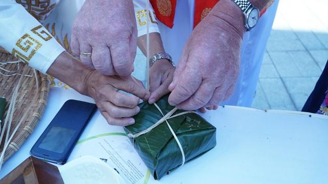 Đôi bàn tay Á hướng dẫn cho đôi bàn tay Âu gói bánh, một thông điệp của sự đoàn kết và thân thiện