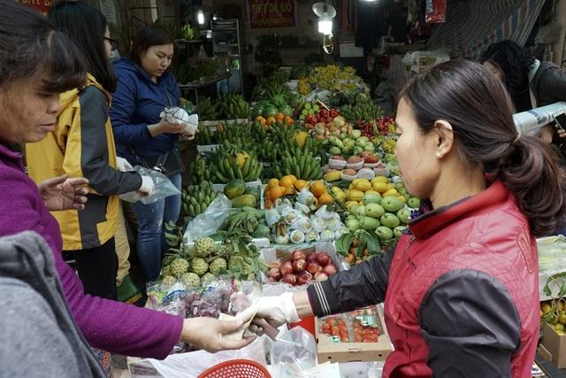 Một cửa hàng bán hoa quả với rất nhiều loại có thể dùng để bày lên ban thờ ngày tết đang tấp nập khách mua.