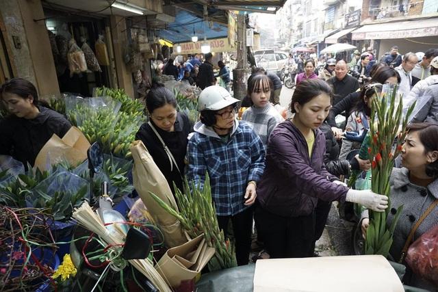 Một cửa hàng bán hoa tươi tại chợ Hàng Bè nườm nượp khách.