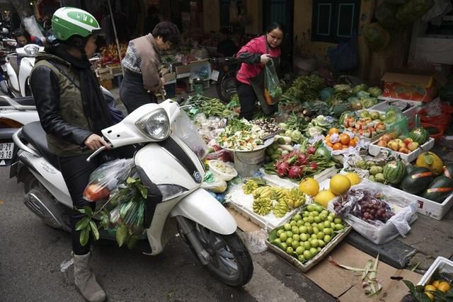 Một phụ nữ với lỉnh kỉnh đủ loại rau quả trên chiếc xe máy của mình.
