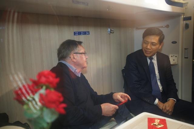 Thứ trưởng Bộ GTVT nói chuyện, chúc mừng năm mới và mừng tuổi cho một vị khách nước ngoài đi chuyến tàu trong đêm giao thừa Tết Mậu Tuất