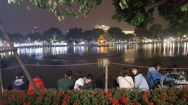Nhiều người đã chọn chỗ và ngồi giữ chỗ bên bờ hồ để chờ xem pháo hoa